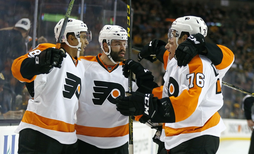 The Flyers' Pierre-Edouard Bellemare (78) celebrates his goal with teammates Radko Gudas (3) and Chris VandeVelde (76) in the first period.