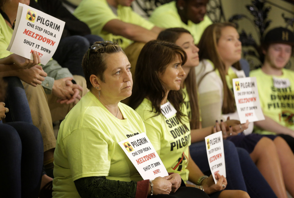 Massachusetts residents Kristin Knowles, bottom row left, and Laura Kelley, center, join others in calling for the closure of the Pilgrim nuclear plant at the Statehouse in Boston.