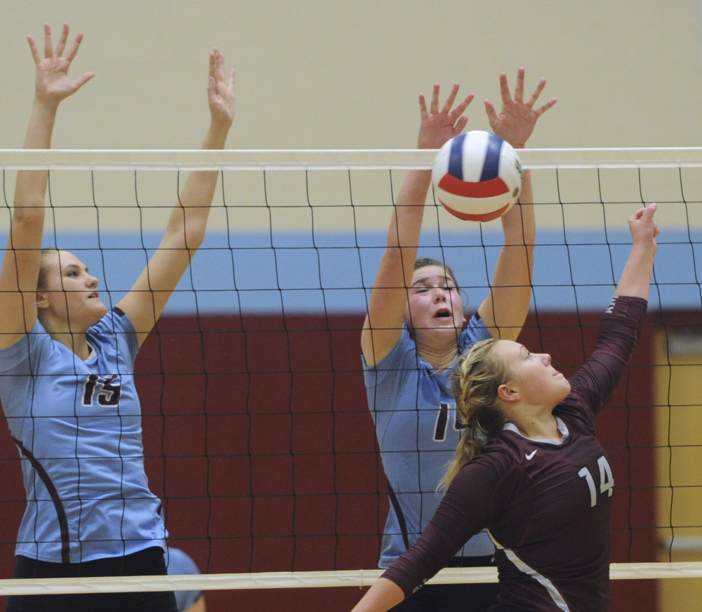 Nataley Jeffrey, left, and Jamie Jannarone of Windham attempt to block a hit by Cassidy Landry of Gorham.