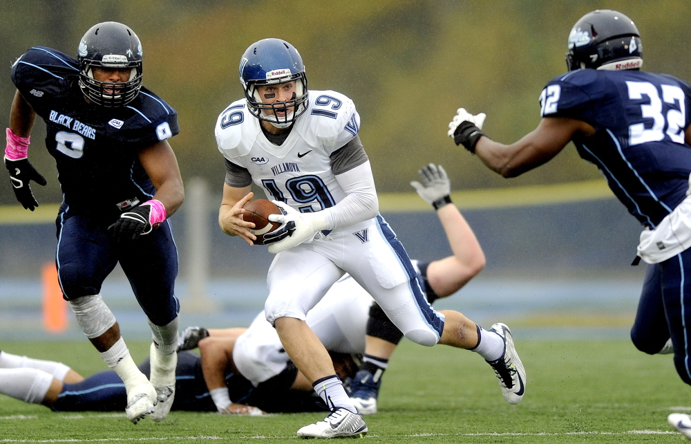 Maine's Trevor Bates, left, has sent a lot of quarterbacks scurrying the last two seasons, including Villanova's John Robertson. Bates is being eyed by pro scouts. 2014 Press Herald File Photo/Gabe Souza