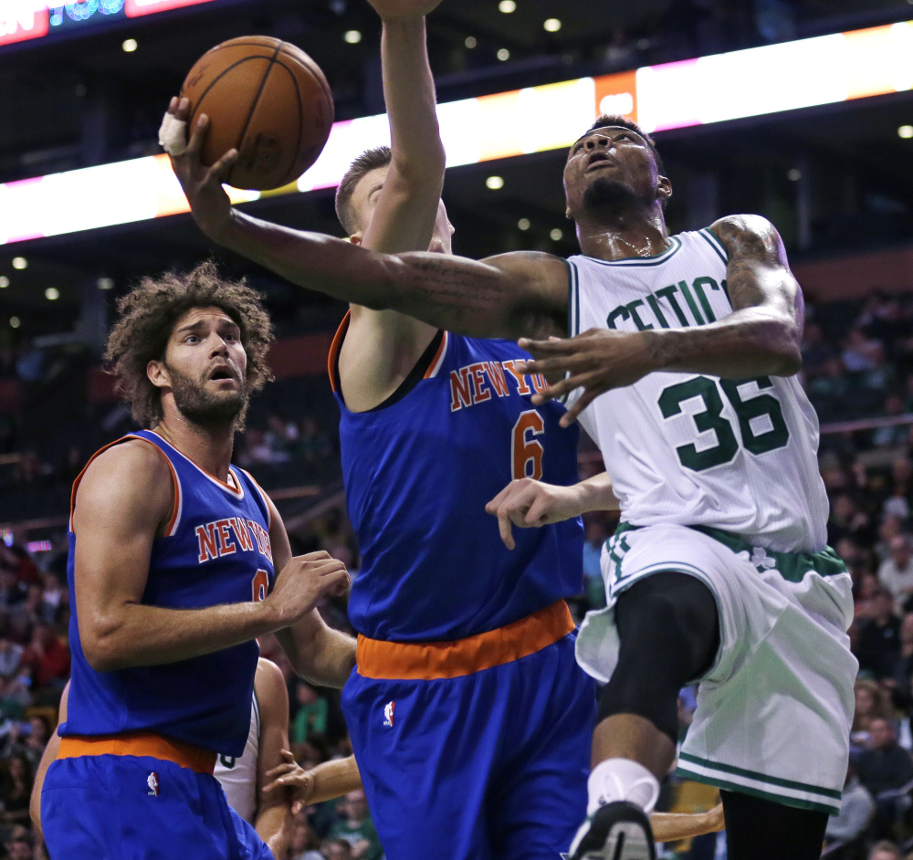 Marcus Smart of the Boston Celtics drives past Kristaps Porzingis, center, and Robin Lopez of the New York Knicks during Boston's 99-85 preseason win Thursday night.