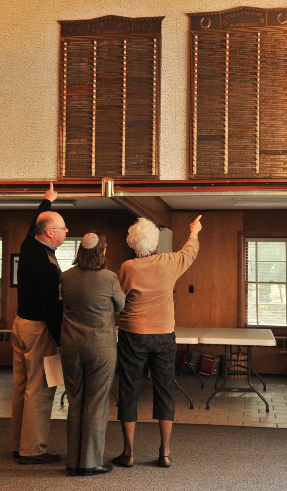 Marty Weiss, left, Rabbi Erica Asch and Charlotte Goos talk about the In Memoriam plaques Wednesday at Temple Beth El in Augusta.