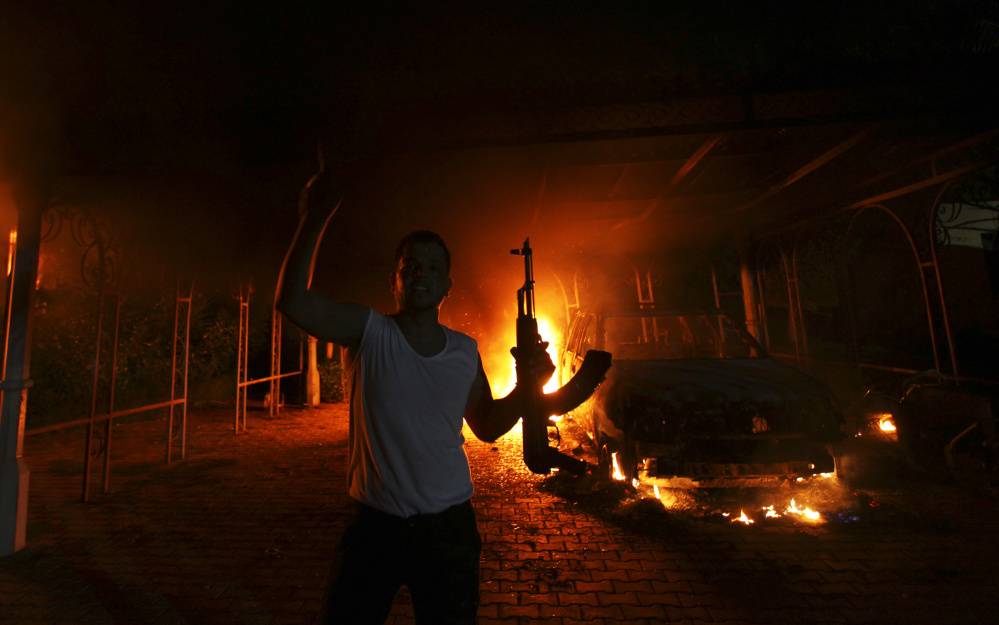A gunman reacts as the U.S. Consulate in Benghazi, Libya, burns on Sept. 11, 2012, after an attack by an armed group. U.S. Ambassador Christopher Stevens and three other U.S. nationals died in the attack. Organized terror groups were later identified as the attackers.