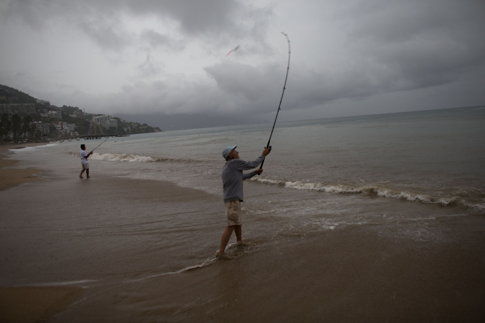 Mike Anderson of Minnesota, right, fishes alongside his friend and local fisherman Miguel Pilas during a steady rain as Hurricane Patricia approaches Puerto Vallarta, Mexico, on Friday