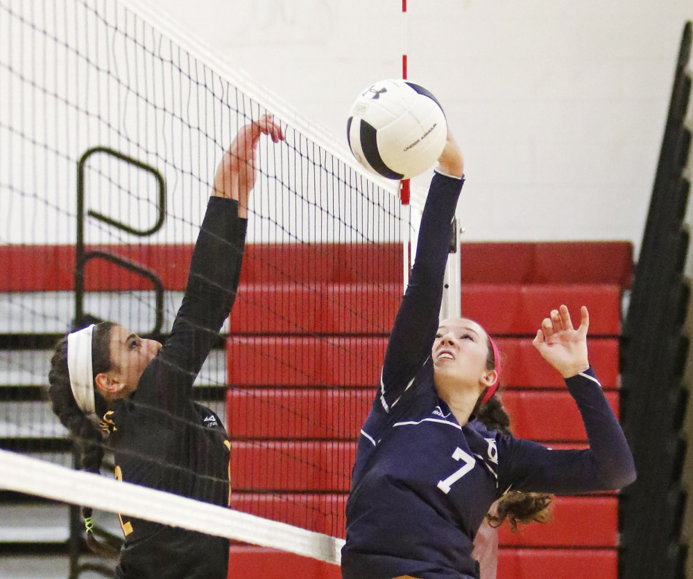 Yarmouth's Liz Clark just misses the volleyball with Cape Elizabeth's Monika Scheindel at the net in a quarterfinal game at Cape Elizabeth on Saturday. Jill Brady/Staff Photographer
