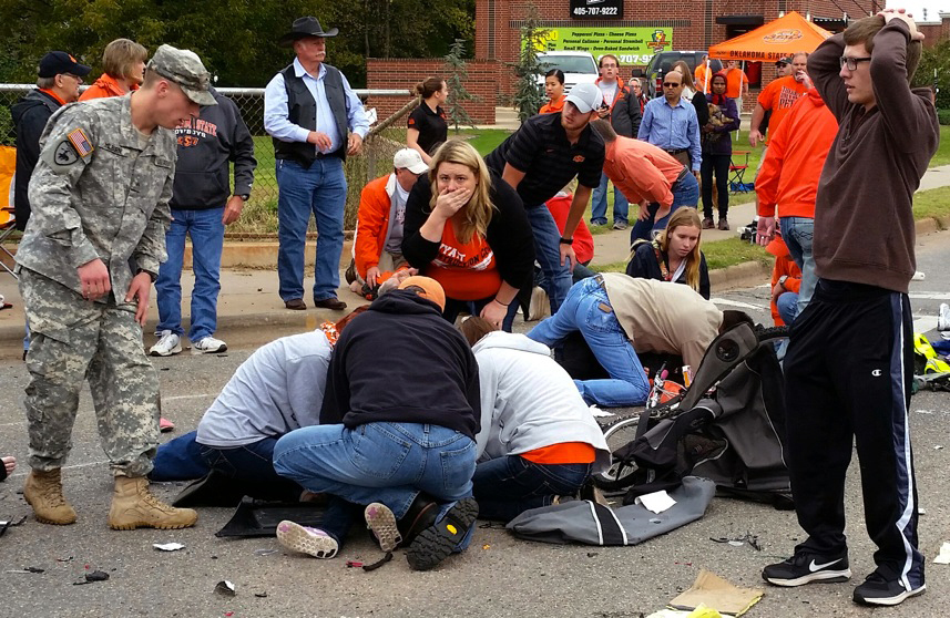 Bystanders help the injured after a vehicle crashed into a crowd of spectators during the Oklahoma State University homecoming parade, causing multiple injuries, on Saturday in Stillwater, Oka.