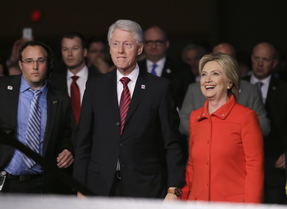 Former President Bill Clinton and his wife, Democratic presidential candidate Hillary Rodham Clinton, walk back to the stage after the Iowa Democratic Party's Jefferson-Jackson fundraising dinner Saturday in Des Moines, Iowa.