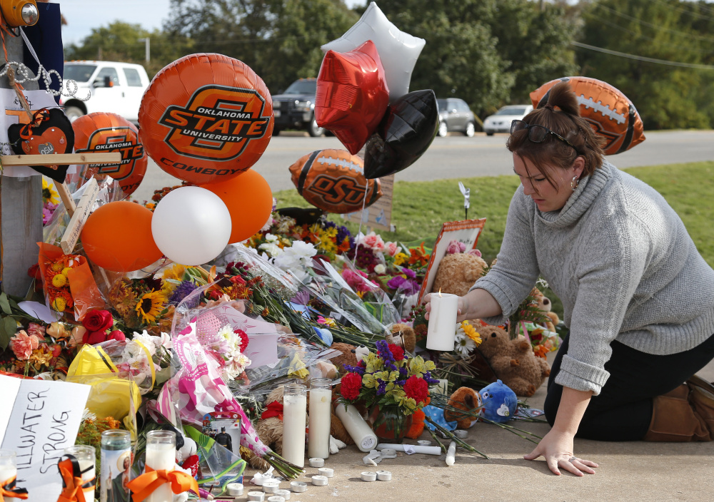 Stefanie Alexander, who witnessed the Saturday homecoming parade crash that killed four, places a candle at a makeshift memorial to the victims in Stillwater, Okla., on Monday.