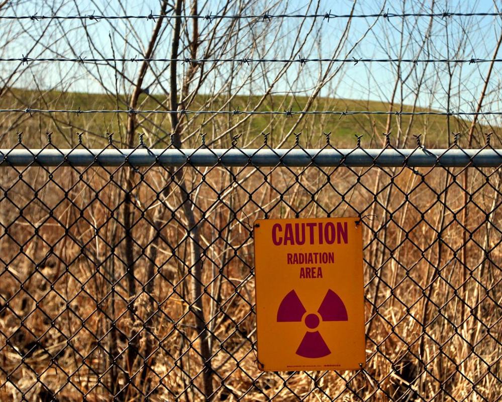 A radiation warning hangs at the West Lake Landfill in Bridgeton, Mo., where officials fear that smoldering embers could spread to where nuclear waste has long been buried.