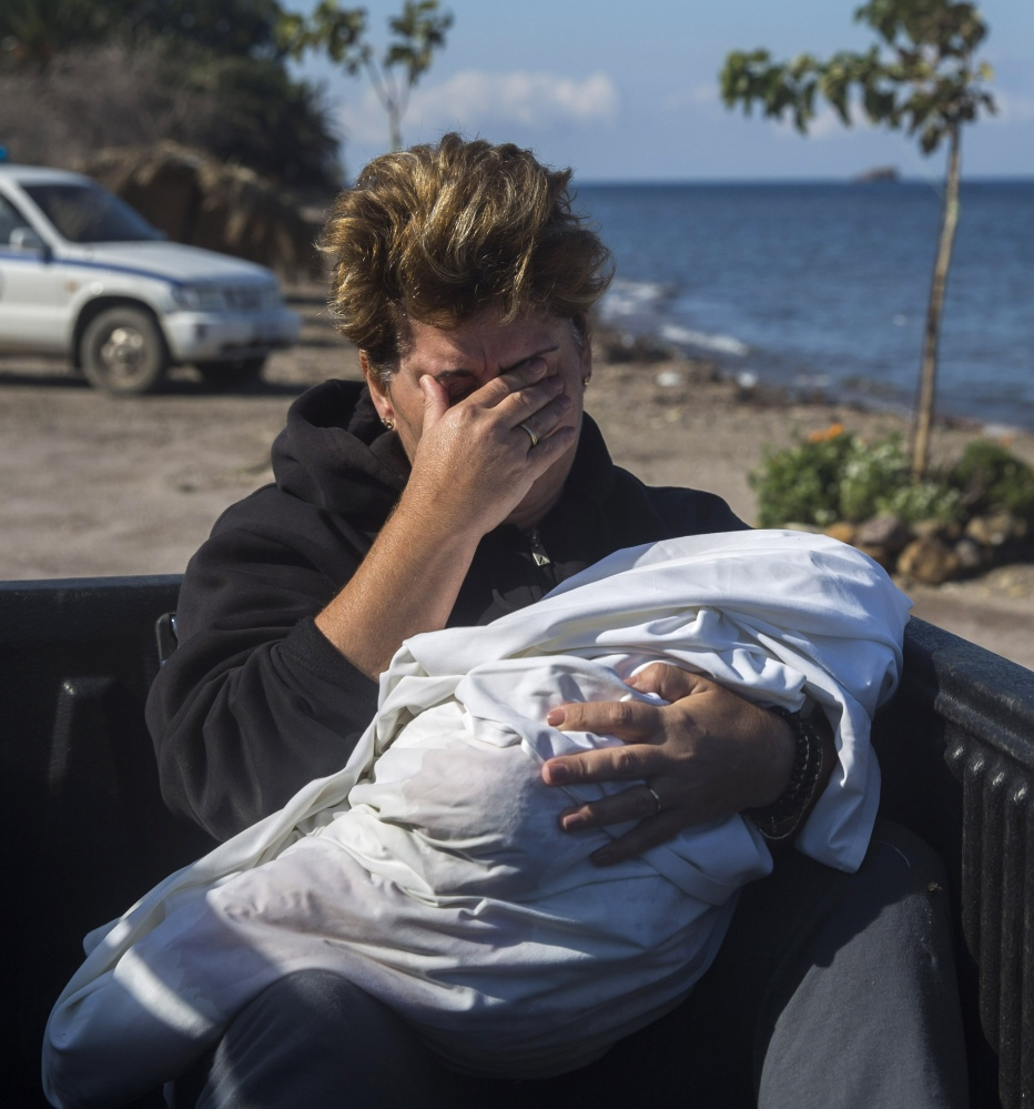 A local resident cries as she holds the body of a dead baby in Petra village on the northeastern Greek island of Lesbos on Friday.