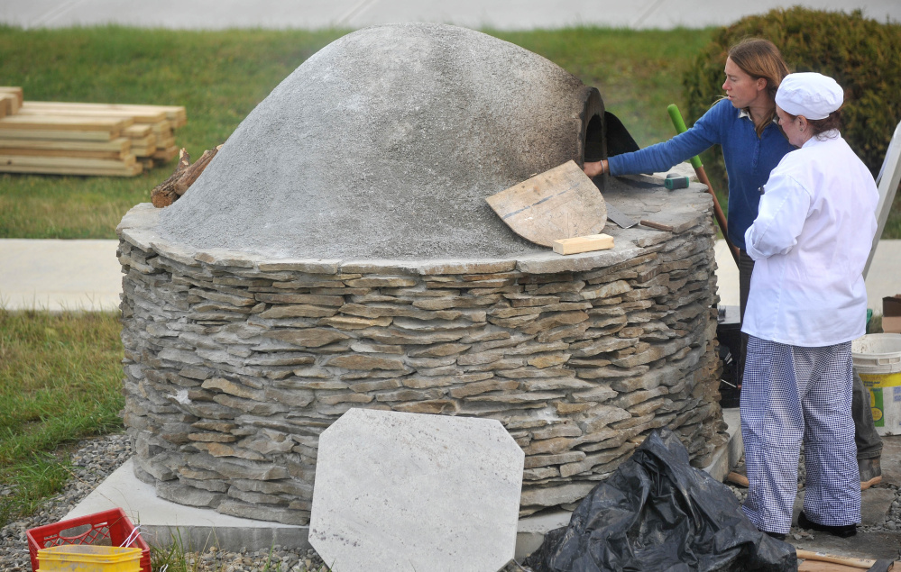 Katherine Creswell, right, farm manager at Kennebec Valley Community College, helps culinary student Brenda Madden with the wood-fired oven at the Alfond campus on Friday.