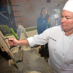 Brenda Madden checks on her calzone in the wood-fired oven during her culinary class at Kennebec Valley Community College on Friday.