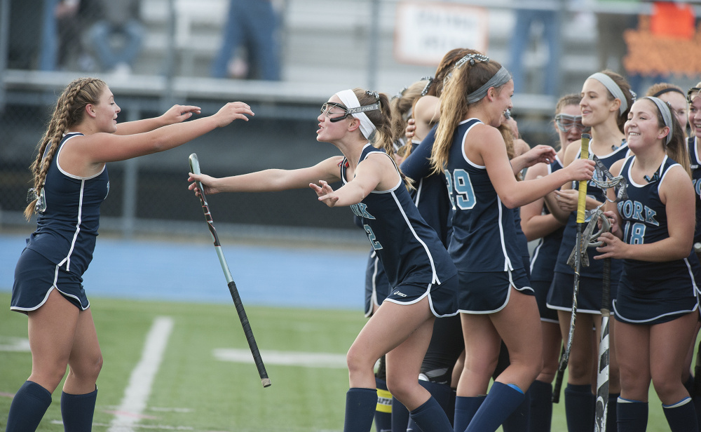 Members of the York girls field hockey team celebrate their 3-2 win over Winslow at the Class B field hockey state championship on Saturday in Orono. The Wildcats have won back-to-back state championships.  Kevin Bennett photo
