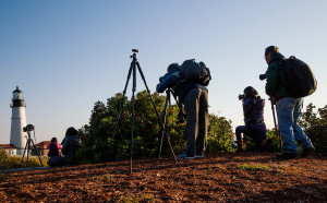Photographic Society of New York members Chen Wen, right, Jane Li, center and Tin Kok, left, set up tripods to photograph Portland Head Light at Fort Williams Park in Cape Elizabeth on Monday.