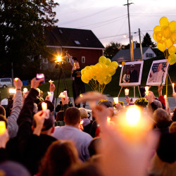 With photos of Dylan Meklin and Danielle Randolph of Rockland on display, residents hold up candles at Monday's vigil for the two missing crew members of the El Faro.