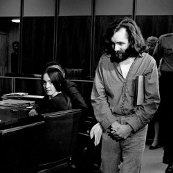 Charles Manson walks into the courtroom in Santa Monica, Ca. on Oct. 13, 1970. Manson and Susan Atkins, seated, a member of his family of followers, are to plead on charges of murdering a Malibu musician, Gary Hinman. When his name was called, Manson stood, folded his arms, and turned his back on the judge. Atkins did the same. The court then entered pleas of innocent. Both are on trial in Los Angeles for killings that included actress Sharon Tate. The Associated Press