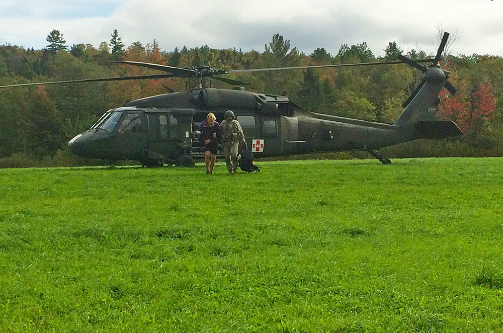 Gabrielle Grace is helped away from the rescue helicopter by a crew member. Courtesy Maine Warden Service