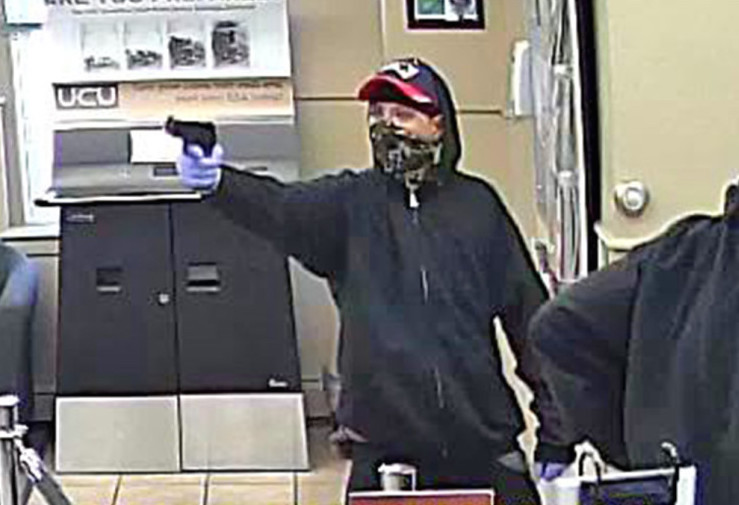 This image from surveillance video shows a robber pointing a gun at the University Credit Union at 391 Forest Ave. in Portland on Sept. 4. A New Hampshire woman has been charged.