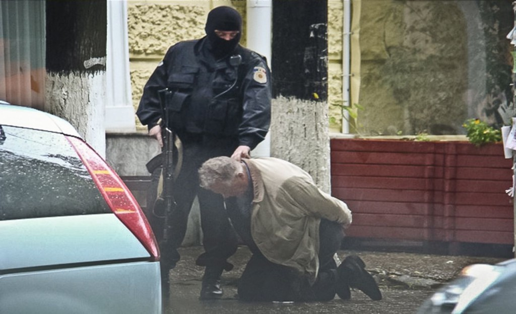 In this June 27, 2011, photo provided by the Moldova General Police Inspectorate, Teodor Chetrus is detained by a police officer in Chisinau, Moldova, during a uranium-235 sting operation. The Associated Press