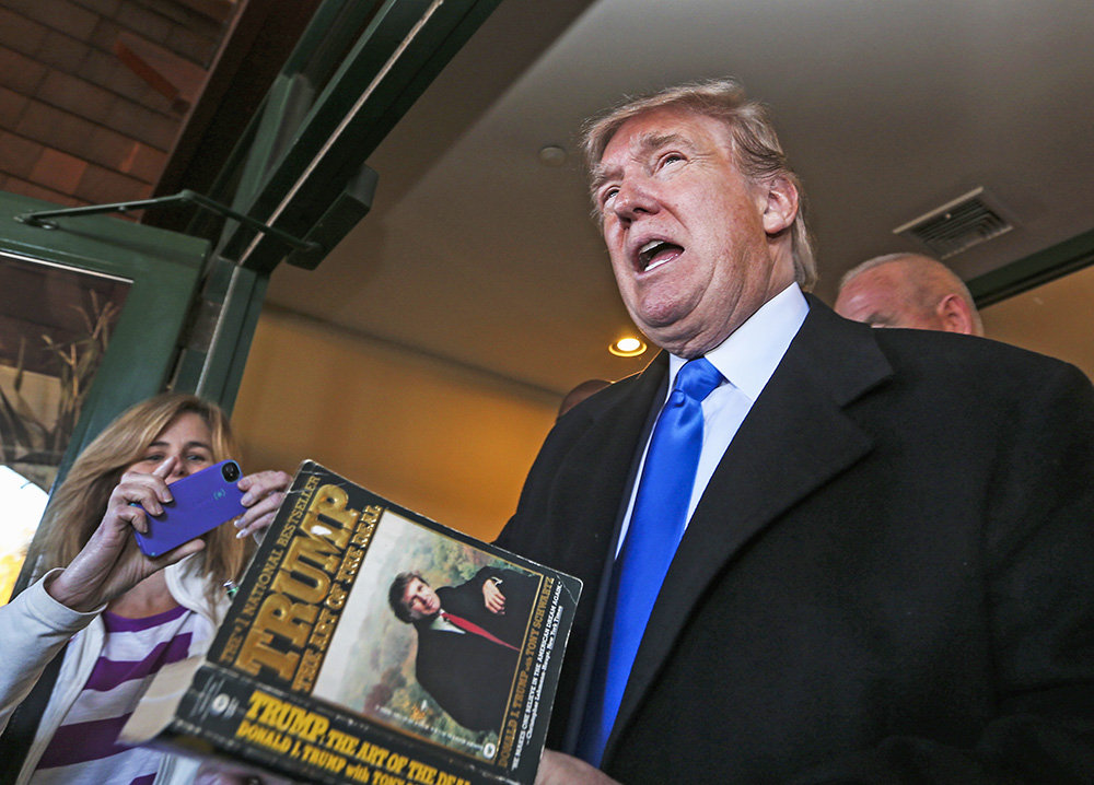 Republican presidential candidate Donald Trump autographs a book on his way out after speaking at a town hall meeting at the Atkinson Country Club in Atkinson, N.H., Monday, The Associated Press