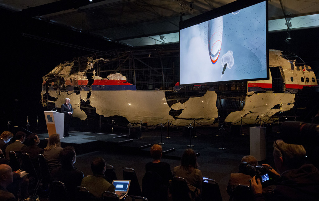 A video show the impact of a missile on Malaysia Airline Flight 17, while a part of the reconstructed forward section of the fuselage is displayed behind, as Tjibbe Joustra, left, head of the Dutch Safety Board presents the board's final report into what caused Malaysia Airlines Flight 17 to break up high over Eastern Ukraine last year, killing all 298 people on board, during a press conference in Gilze-Rijen, central Netherlands, Tuesday. The Associated Press