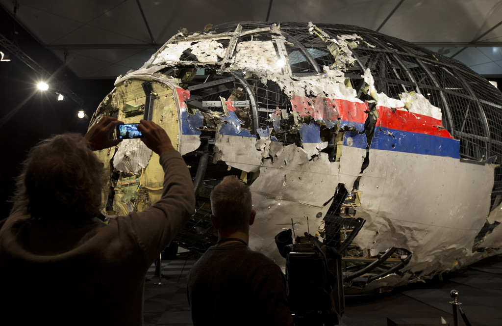 Journalists take images of part of the reconstructed forward section of the fuselage after the presentation of the Dutch Safety Board's final report. The Associated Press