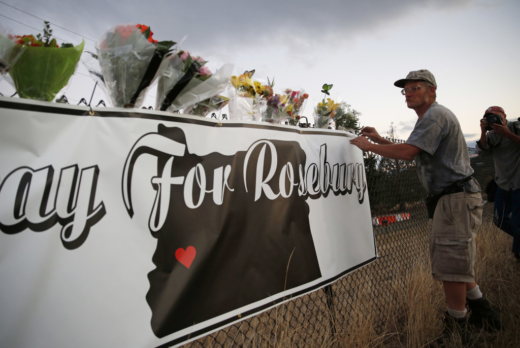 Michael Garwood places flowers Friday at a makeshift memorial near the road that leads to Umpqua Community College, in Roseburg, Ore. The small town is the latest U.S. community to experience the horror of a mass shooting. The Associated Press