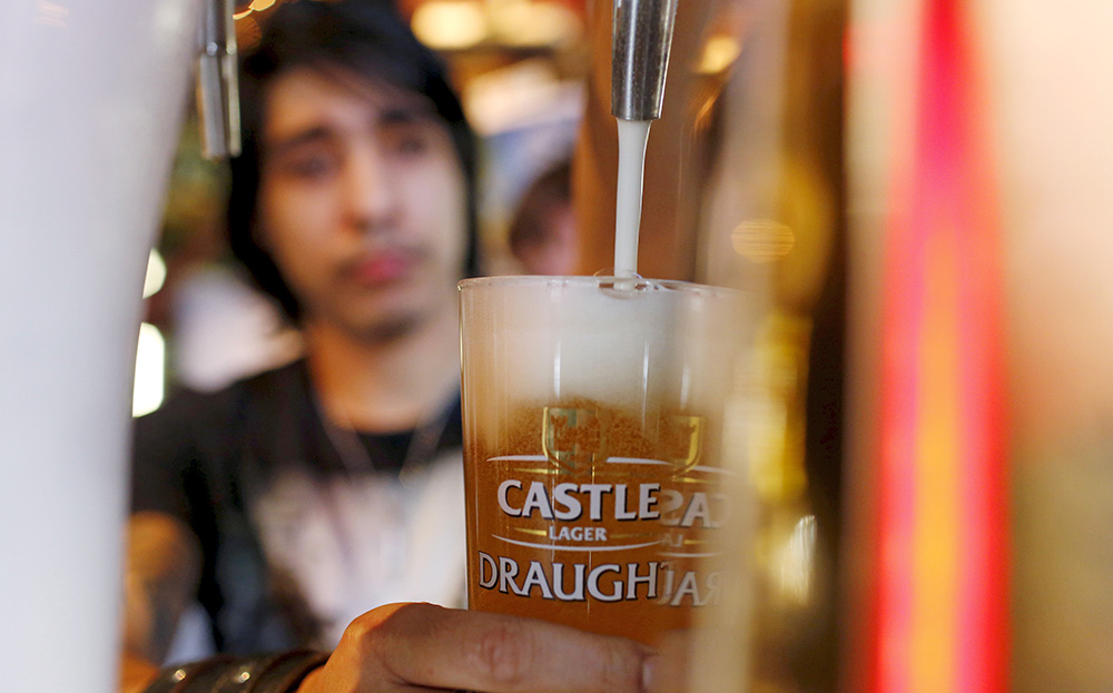 A barman pours a beer produced by brewing company SAB Miller at a bar in Cape Town recently.  If  the merger of Anheuser-Busch InBev and rival SABMiller goes through, the company will have a market value of about $275 billion and produce a third of the world's beer, combining AB InBev's dominance of Latin America with SABMiller's dominance in Africa, both fast-growing markets. Reuters