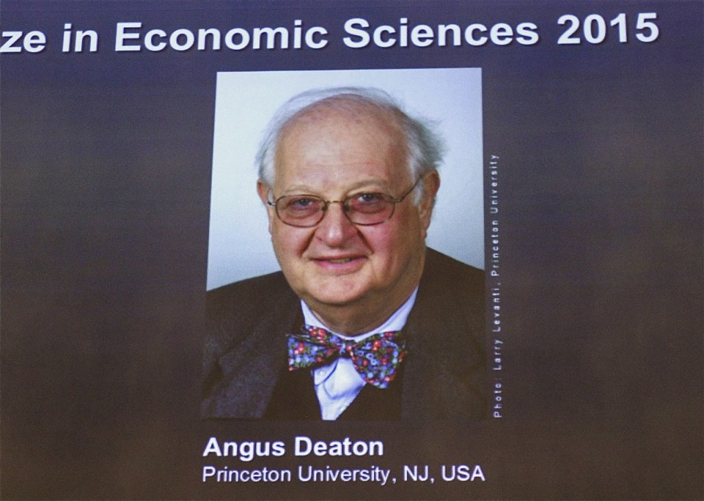 Angus Deaton's photo is projected on a screen at the Royal Swedish Academy of Sciences. The Associated Press