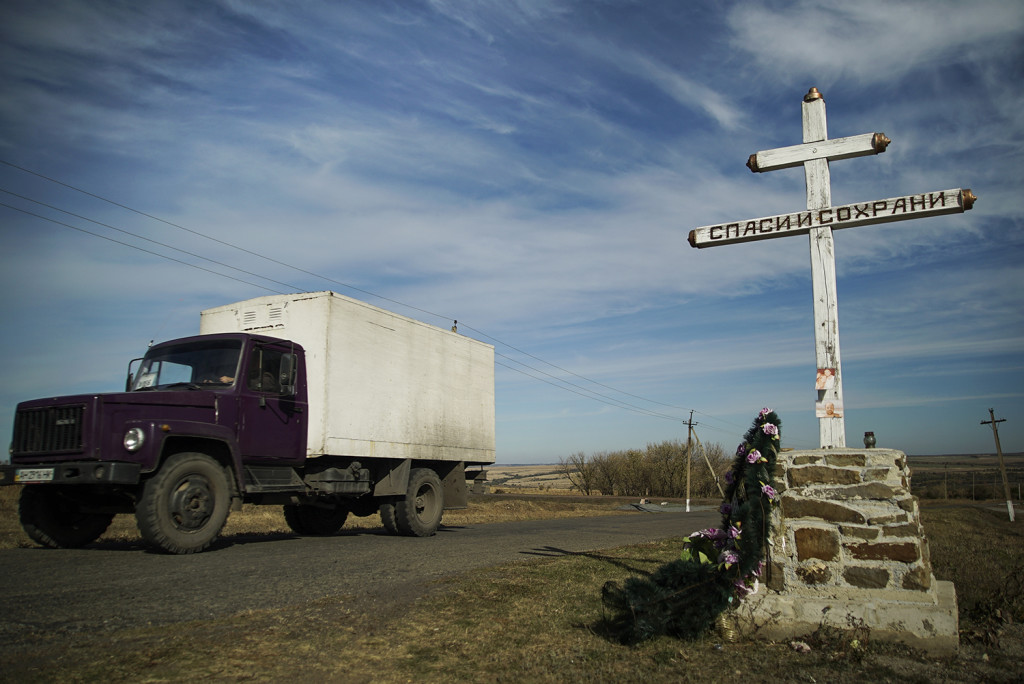 A truck drives by an Orthodox cross with a sign reading Save and Guard, at a memorial to the victims of the Malaysian Airlines MH17 plane crash,  near the village of Hrabove, eastern Ukraine, Tuesday Oct. 13. The Associated Press
