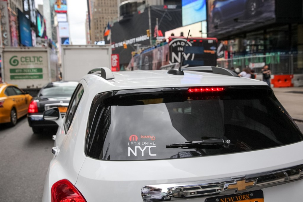 "A car from GM's ""Let's Drive NYC"" car-sharing program sits in traffic near Times Square. In the new GM business venture, announced in an investor call on Thursday, October 1, 2015, customers can use a mobile app to reserve a shared  vehicle and access parking in 200 garages citywide."