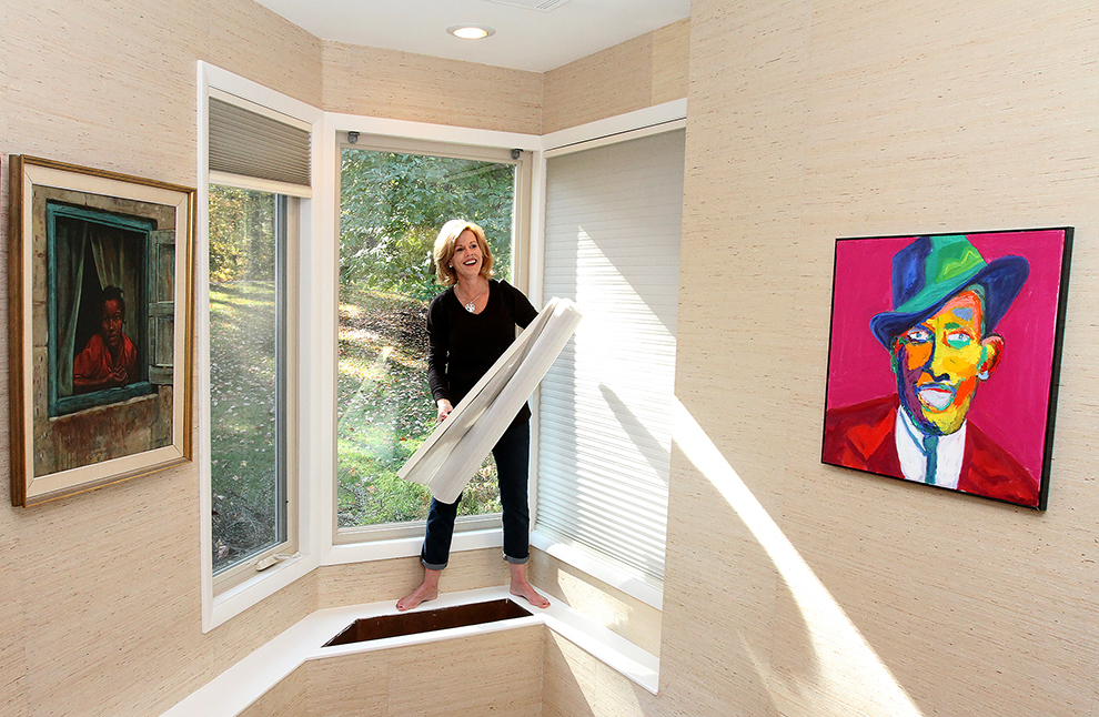 Elizabeth Polansky, owner of The Styled Home removes non functioning blinds to let in more natural light at 35 Buttonwood Lane.