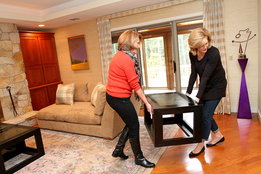 Elizabeth Polansky, owner of The Styled Home, right relocates a piece of furniture with employee Holly McQuinn, a staging assistant while preparing 35 Buttonwood Lane in Portland to be photographed.