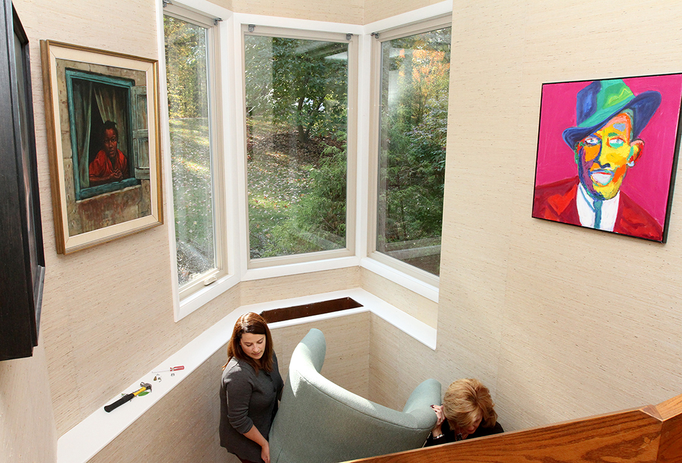 Jill Butler, left, marketing manager at Dambrie Garon Real Estate Experts at Keller Williams Realty helps Elizabeth Polansky, owner of The Styled Home,  relocate a piece of furniture while preparing 35 Buttonwood Lane in Portland to be photographed.