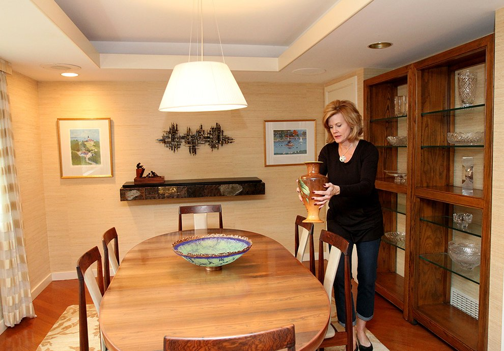 Elizabeth Polansky, owner of The Styled Home, carefully removes a vase from the dining room shelving to use elsewhere in the home while preparing 35 Buttonwood Lane in Portland to be photographed.