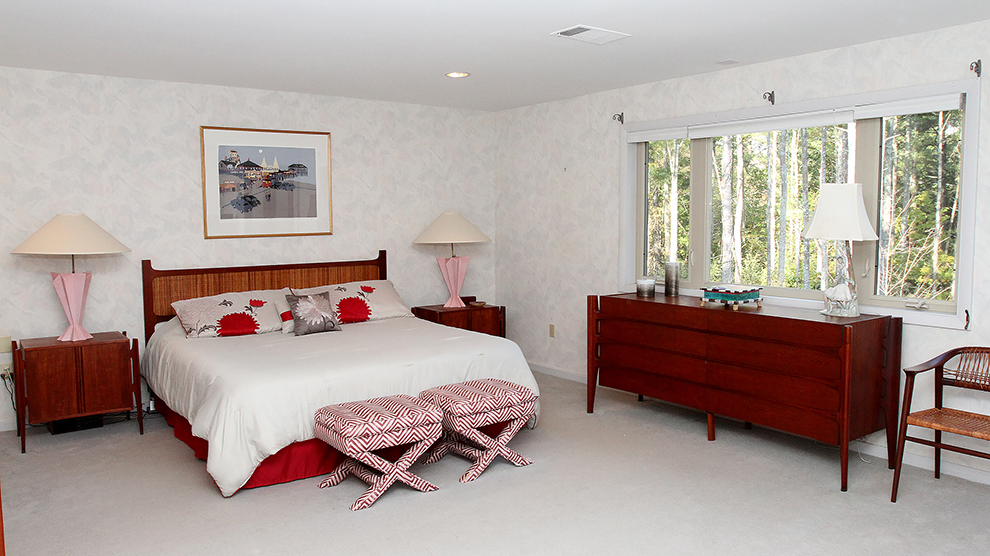 The master bedroom at 35 Buttonwood Lane in Portland after it is staged by The Styled Home using the owners possessions. The bedding was flipped over to neutralize some of the red. Outdated window treatments were removed and fabric that was draped over the stools was removed.