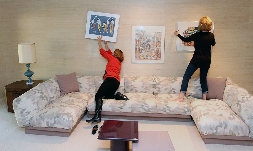 Holly McQuinn, left, a staging assistant at The Styled Home and Elizabeth Polansky, the owner, rearranges artwork while preparing 35 Buttonwood Lane in Portland to be photographed.