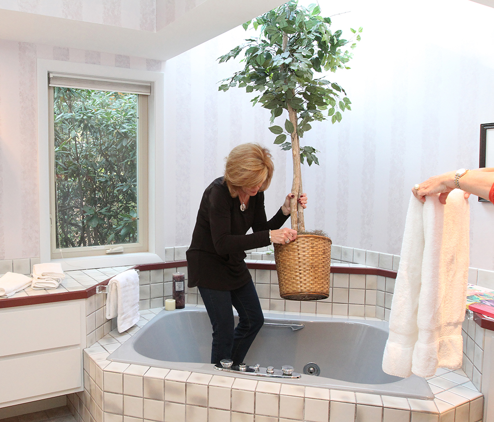 Elizabeth Polansky, owner of The Styled Home, left, removes a silk ficus from the master bath, while employee Holly McQuinn folds towels while preparing 35 Buttonwood Lane in Portland to be photographed.