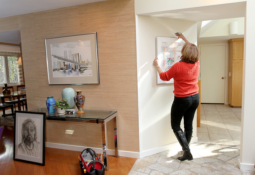 Holly McQuinn,  a staging assistant at The Styled Home hangs a piece of artwork at  35 Buttonwood Lane in Portland.