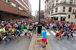 Hundreds of runners bolt down Congress Street at the start of the 4-mile race through downtown Portland.