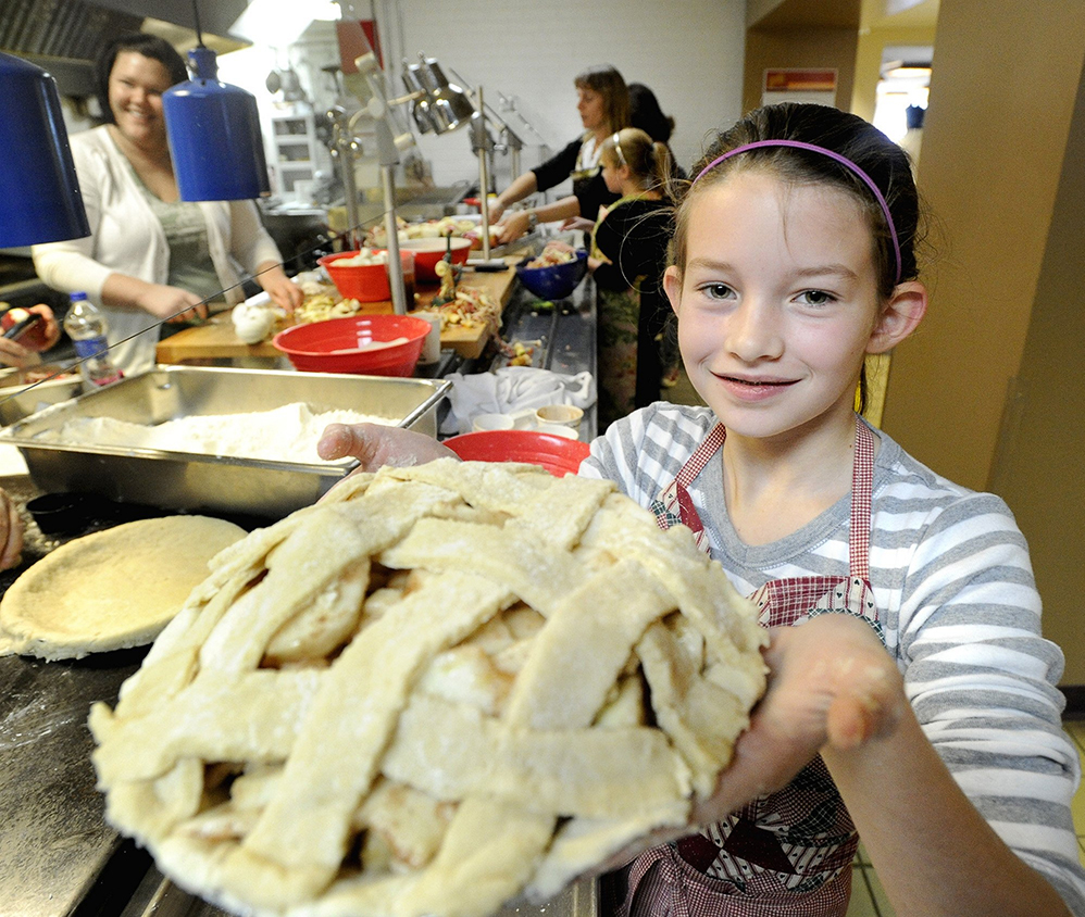 Grace Perron holds a finished apple pie at St. Joseph's College in Standish to give out at a local food pantry in November 2010.