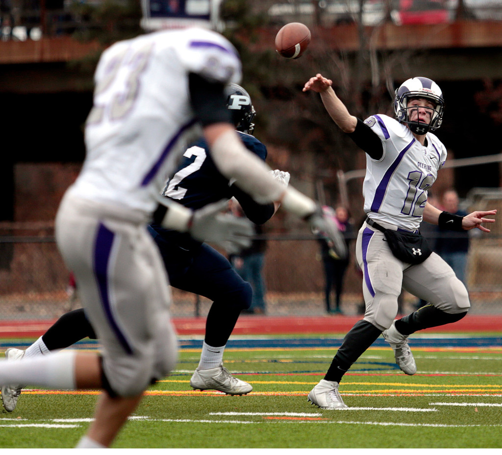 PORTLAND, ME - NOVEMBER 26: Deering quarterback Max Chabot tries to evade pressure as he gets a pass off intended for Patrick Viola, foreground, during the 104th annual Deering vs. Portland Thanksgiving Day football game at Fitzpatrick Stadium Thursday, November 26, 2015. The pass fell incomplete. (Photo by Gabe Souza/Staff Photographer)