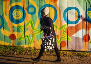 NOV. 17: Bryn Arbuckle of Portland walks in front of a colorfully painted fence on Cumberland Avenue in Portland.