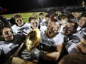 Yarmouth vs Winslow in the Class C state championship football game at Fitzpatrick Stadium. Alexander Clark of Winslow hoists the gold ball while celebrating with teammates following their 24-10 victory over Yarmouth. Derek Davis/Staff Photographer