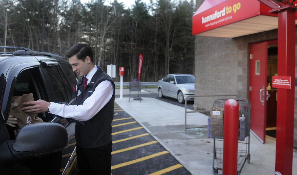 Hannaford employee Matt Pazdziorko hands customer Priscilla Zarella, of Readfield, items she ordered Monday from the Hannaford on the Whitten Road in Augusta at the new drive up delivery spot. For a $5 service fee if the order is less than $125, customers can order items and pick them up outside the store. If the order is more than $125, the service is free.