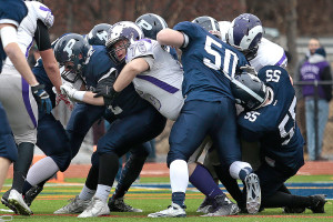 Portland and Deering players battle in the teams' 104th Thanksgiving Day game. From left for Portland are Ethan Hoyt (52), Dan Marzilli (50) and Charles Kovarik, (55), while Deering's Mike Darling (76) pushes the middle of the pile.