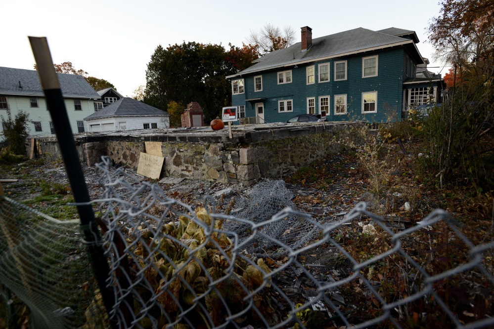 PORTLAND, ME - OCTOBER 27: The foundation is all that remains at the fenced in lot on Noyes St. in Portland where six people lost their lives in a fire in 2014. Photographed Tuesday, October 27, 2015. (Photo by Shawn Patrick Ouellette/Staff Photographer)