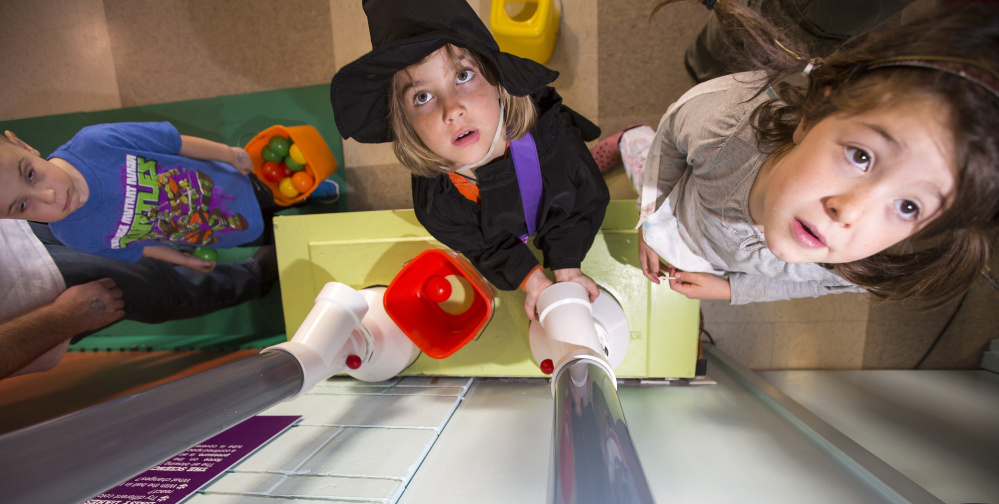 From left, Lewis Walker, Sophie Knoll, and Caroline O'Brien watch Saturday as balls are lifted into pneumatic tubes at the Children's Museum & Theatre of Maine in Portland.