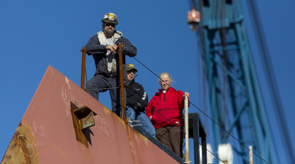 Production workers at Bath Iron Works stand on the bow of the in-progress USS Michael Monsoor during a christening ceremony Saturday. Workers are being pulled off projects to work on the USS Zumwalt, which is a year behind schedule.