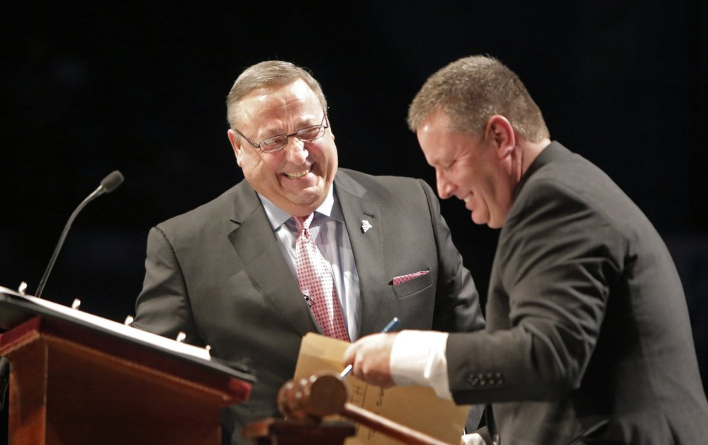 Gov. Paul LePage laughs with Senate President Mike Thibodeau after signing paperwork after LePage took the oath of office at his inauguration at the Augusta Civic Center on Jan. 7, 2015. A rift has since opened between the two.